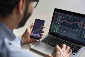 Businessman trader investor analyst using mobile phone app analytics for cryptocurrency financial market