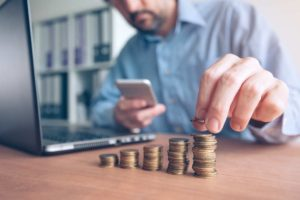 Finances and budgeting, businessman stacking coins for todays market report
